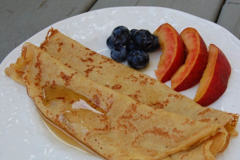 Two crepes on a plate with peach slices and blueberries.