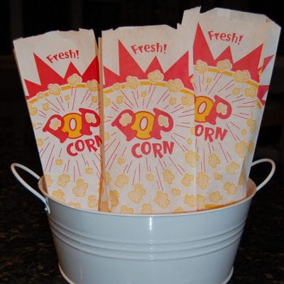 Three popcorn bags sitting in a white metal container.