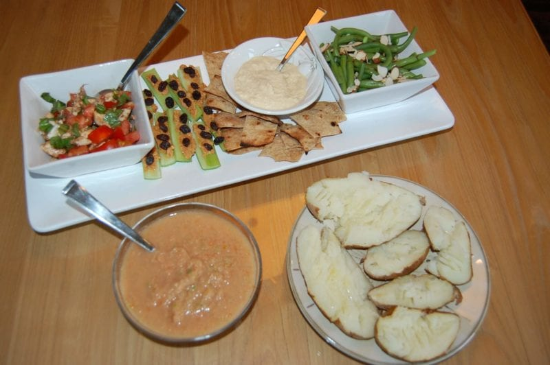 Crackers and hummus, baked potatoes, green beans, and a bowl of gazpacho plated on the dinner table.
