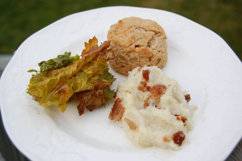 Kale chips, mashed potatoes, and whole-wheat biscuit on a plate.