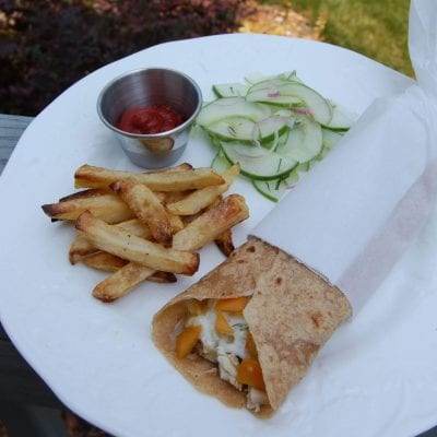Homemade whole-wheat tortillas with cucumber salad and baked french fries with ketchup on a plate.