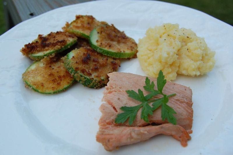 Salmon, breaded zucchini, and mashed potatoes on a plate.