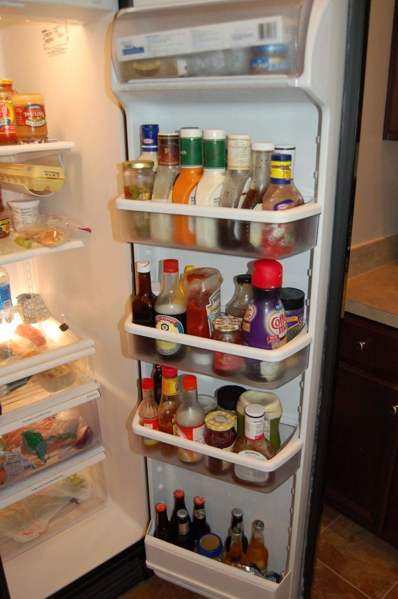 The inside of a refrigerator door that has tons of highly processed condiments and salad dressings.