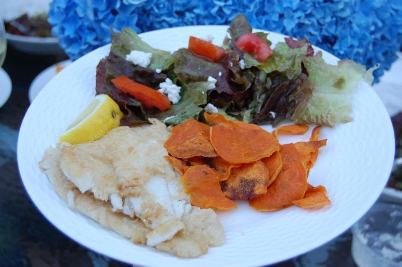 Baked sweet potato chips, sautéed fish, and a salad on a plate.