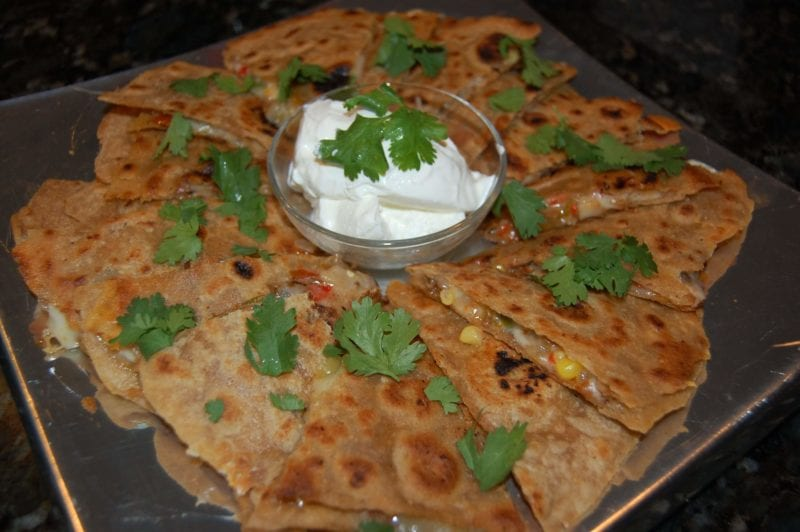 Quesadillas with a small bowl of sour cream on a plate.