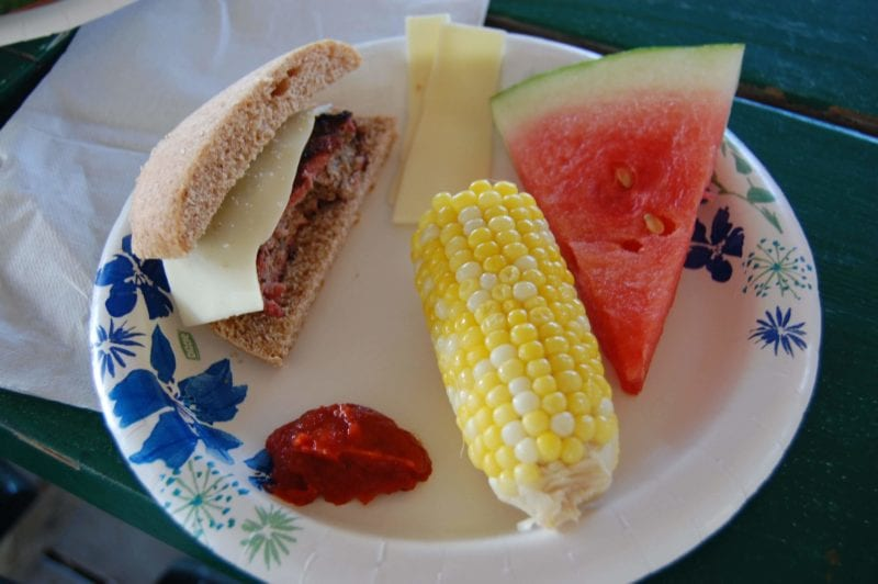 Hamburger, ear of corn, and a slice of watermelon on a plate.