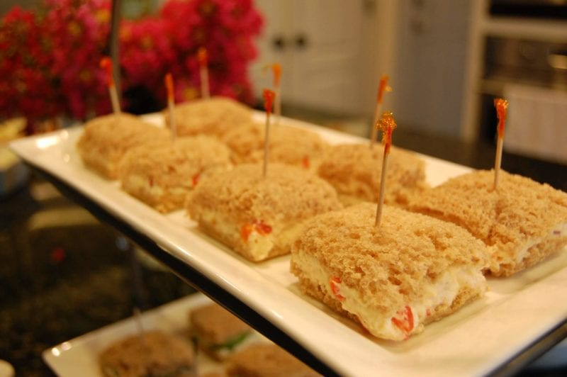 Pimento cheese and cucumber dill tea sandwiches on a plate.