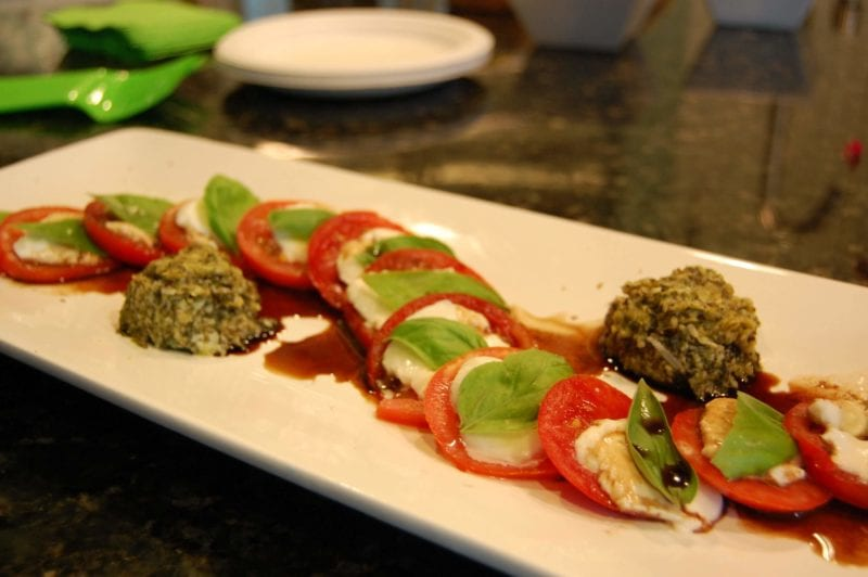 Caprese salad with pesto sauce on a plate.