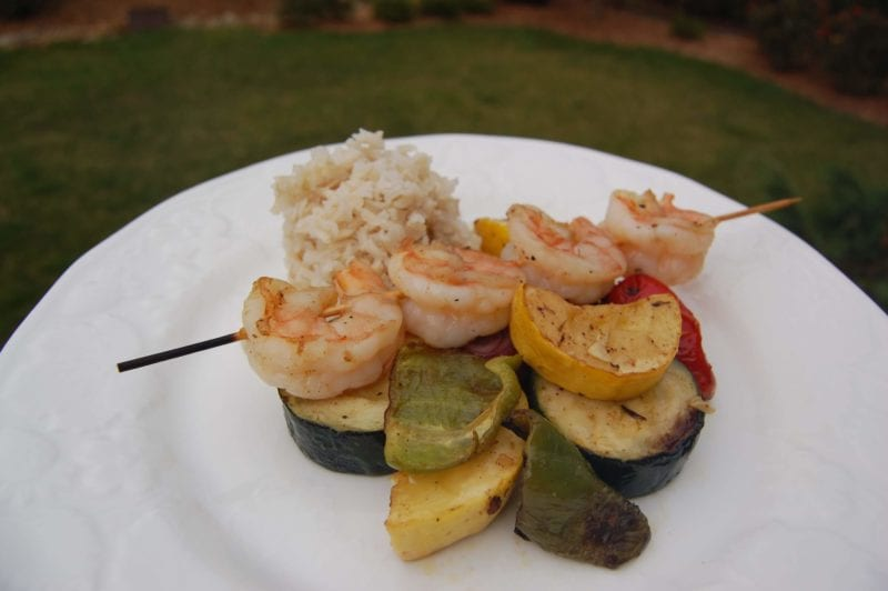Shrimp & vegetable kabobs over brown rice on a plate.