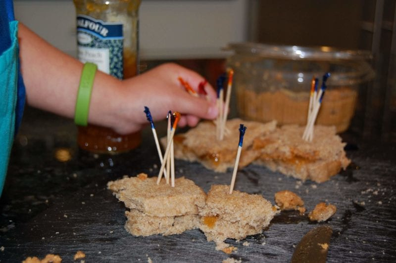 Peanut butter and jelly sandwiches made by a toddler with toothpicks in the center.