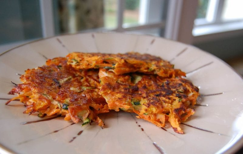 Potato pancakes made with sweet potato and shredded zucchini on a plate.