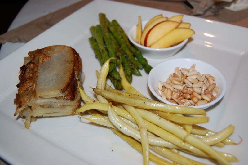 Peaches and toasted pine nuts, green beans, asparagus, and potato gratin on a plate.
