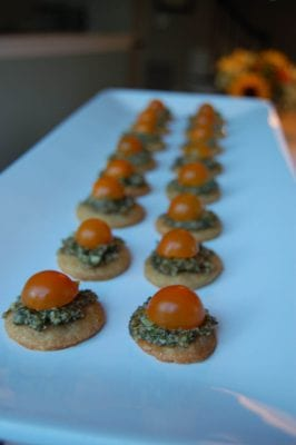 Homemade parmesan cheese crisps topped with pesto and sun gold tomatoes.
