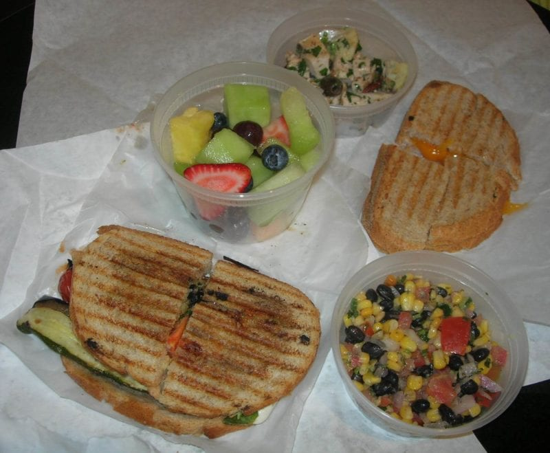 A variety of food ordered from a restaurant that includes a Mediterranean grilled vegetable and mozzarella sandwich, fresh fruit, grilled cheese sandwich, Greek chicken salad, and corn/black bean/tomato salad.