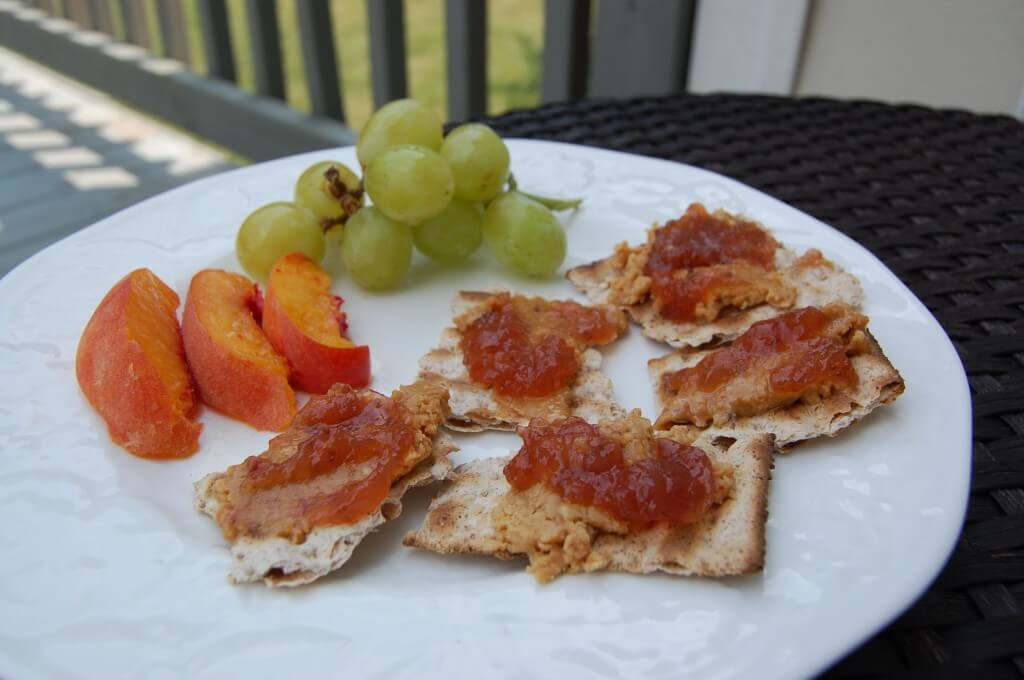 Matzo crackers with peanut butter and jelly on top with a side of peaches and grapes.
