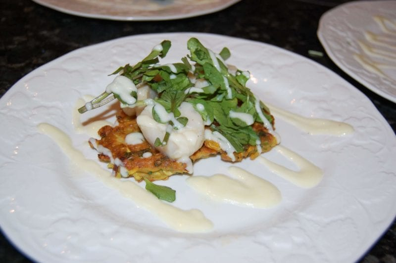 Seared scallops, squash fritters, and lime yogurt sauce topped with some greens.