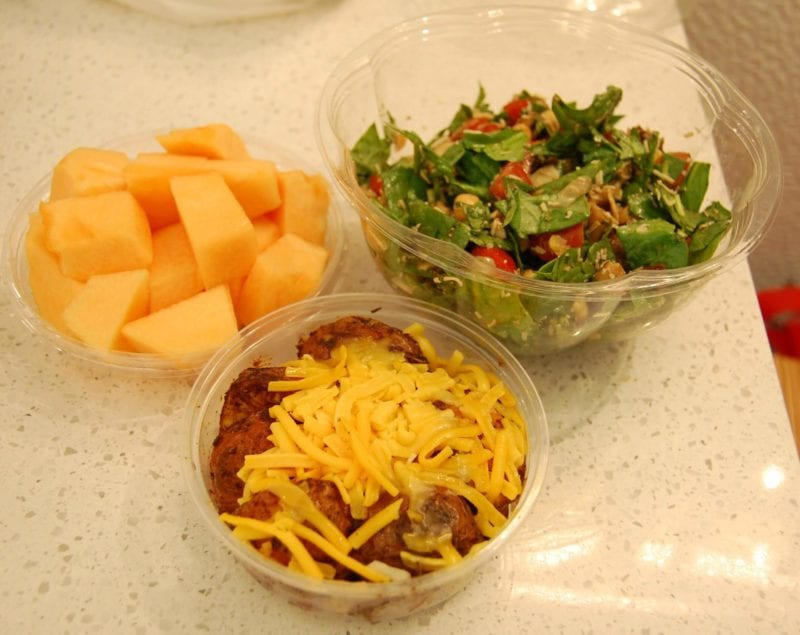 A hearty salad, cantaloupe, and roasted potatoes topped with grated cheese packed in containers from Toasties deli in NYC.