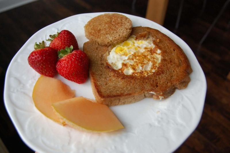 Whole-wheat toast with egg fried in the middle with a side of strawberries and cantaloupe.