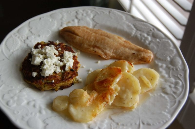 Fish, squash fritters topped with goat cheese, and potato gratin on a plate.