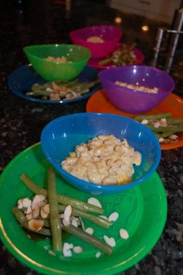 Plates of homemade macaroni and cheese and greenbeans.