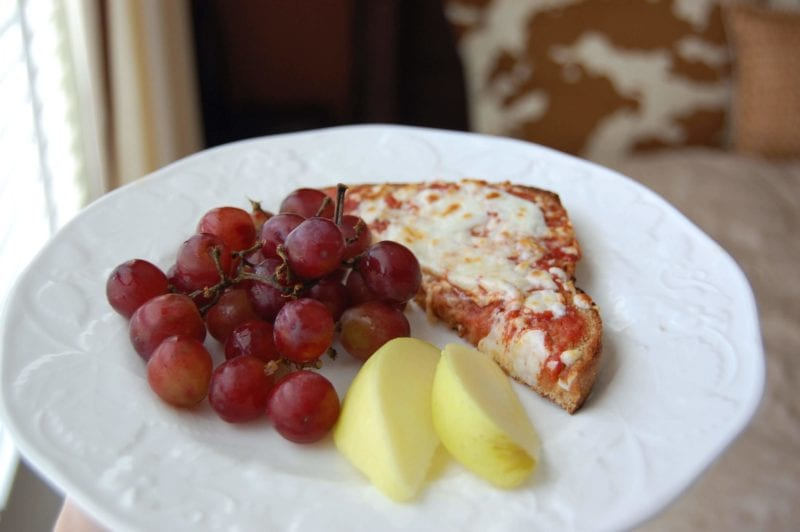 Homemade toast pizza with a side of grapes and apples on a plate.