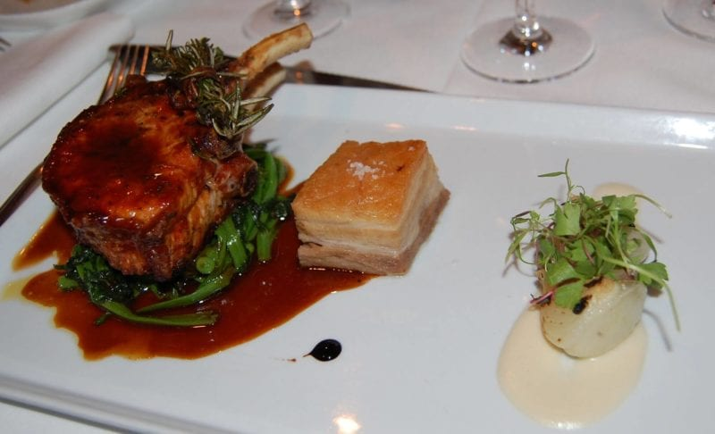 Pork chop on a bed of greens on a plate served at Gotham Bar & Grill in NYC.
