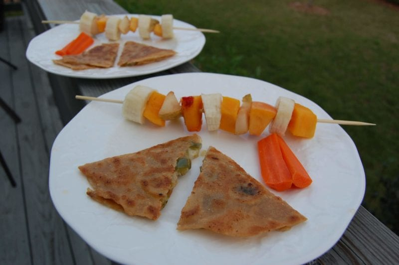 Homemade quesadillas and fruit kabobs on a plate.