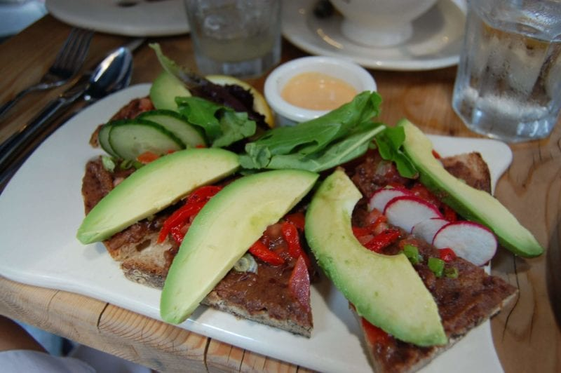 An open faced sandwich with black bean spread and avocado on whole-wheat bread.