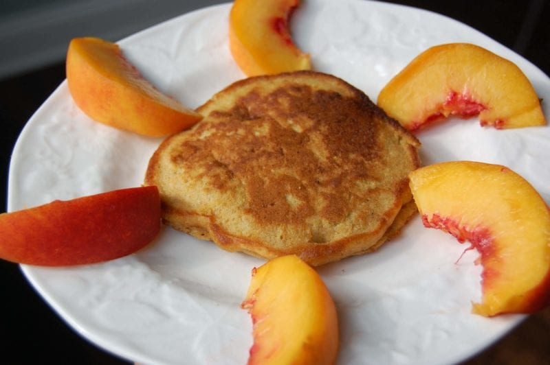 Homemade banana pancakes with sliced peaches around it in the shape of a sunshine.