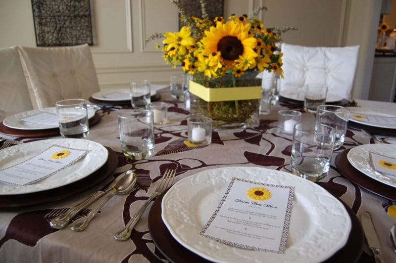 Table setting for guest with a beautiful bouquet of sunflowers in the center.