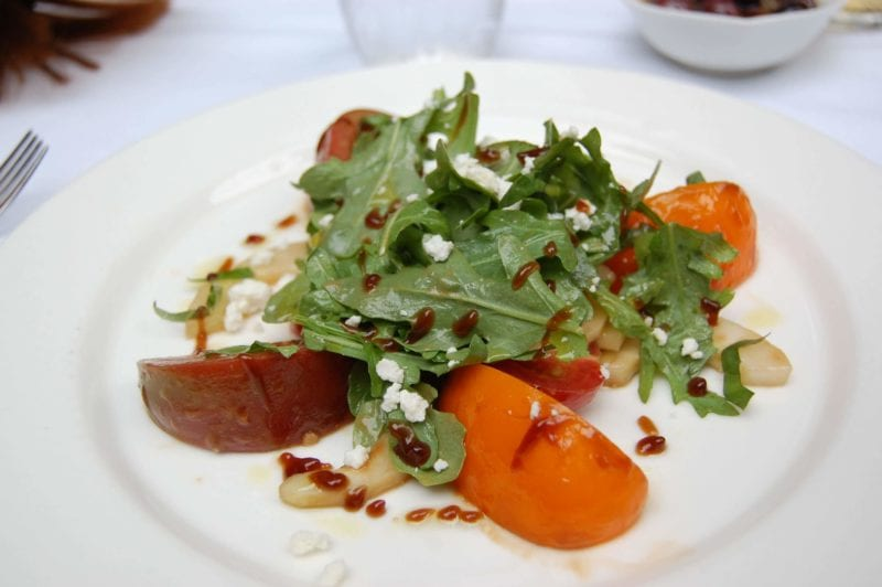 A small plate of arugula, sliced fruit pieces, blue cheese crumbles and dressing.