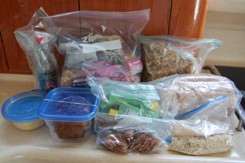 Homemade food and snacks packed in ziplock bags and plastic containers.