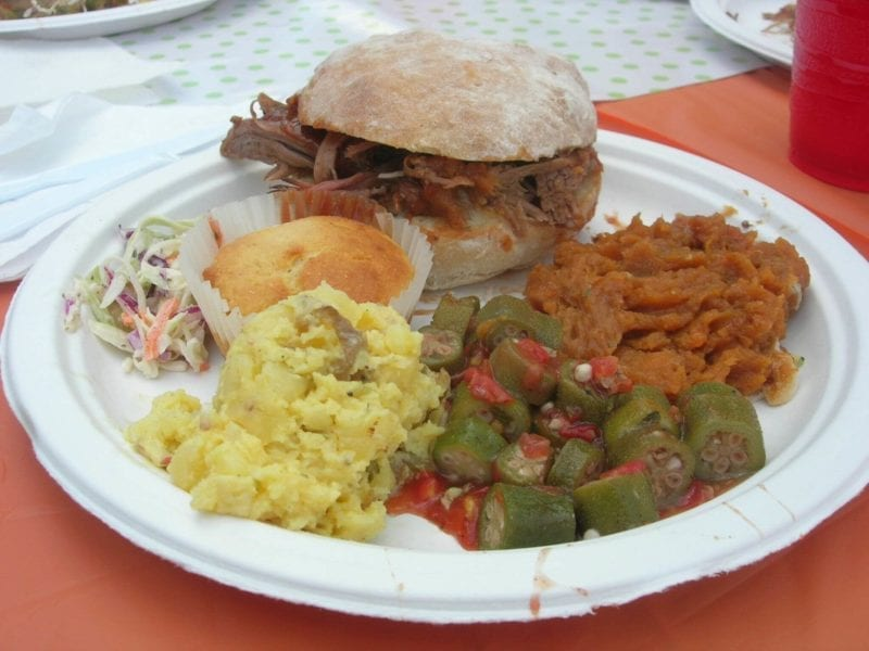 Plate of pulled pork on a bun, potato salad, corn bread muffin, coleslaw, and mashed sweet potatoes.