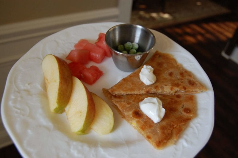 Homemade cheese and corn quesadillas with a side of fruit and frozen peas on a plate.