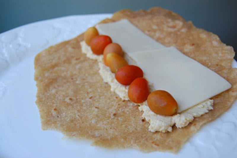 Homemade whole-wheat tortillas with hummus, cheddar cheese, and tomatoes on a plate.
