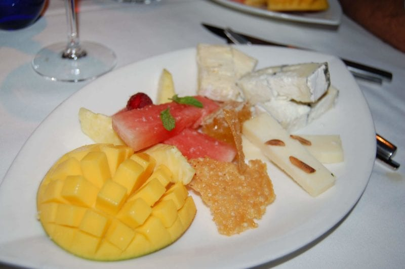 Plate of different cheeses, fruit, honeycomb, and Parmesan crisps from Upstream in North Carolina.