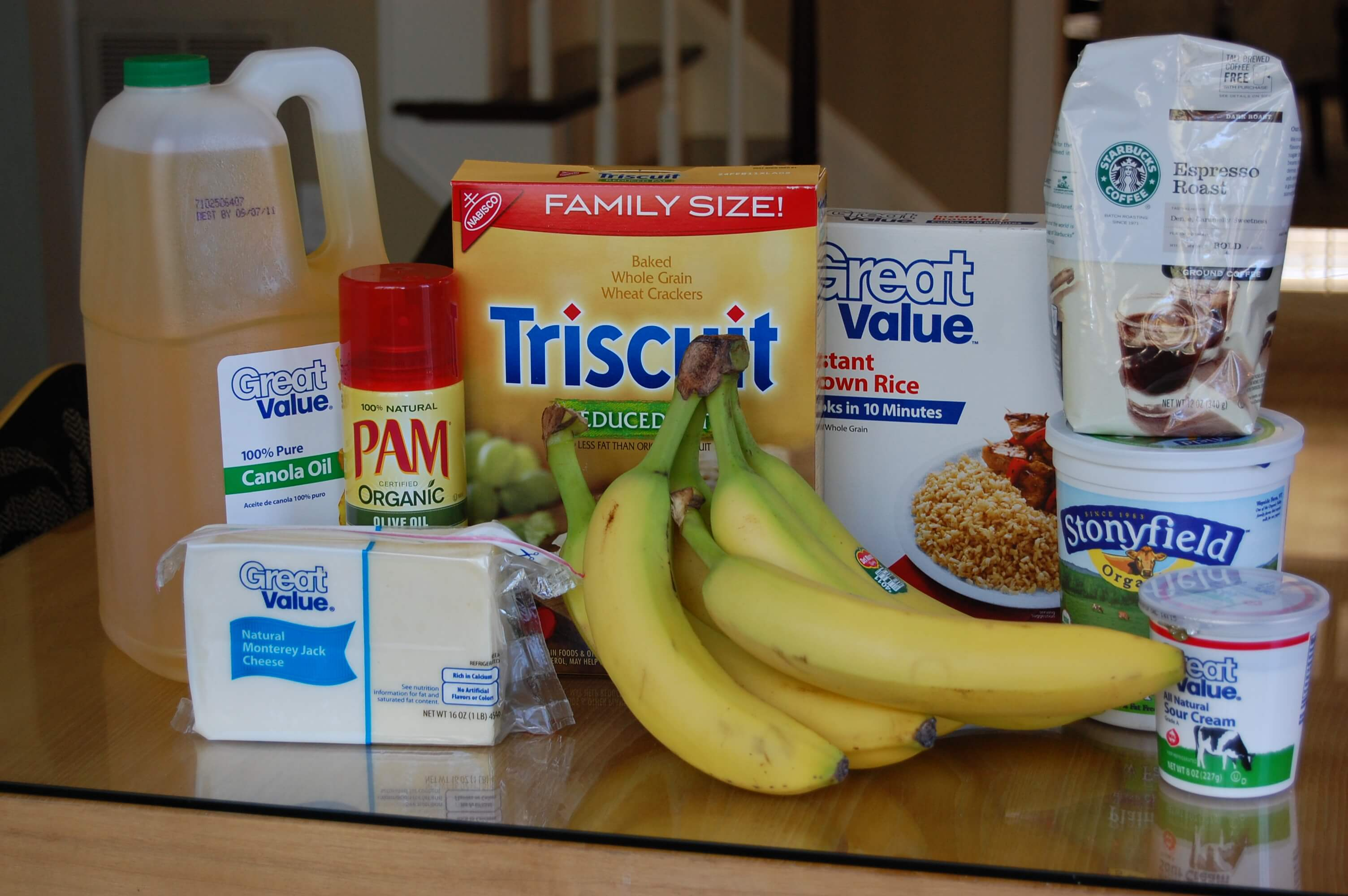 Groceries from Wal-Mart on a table that include coffee, bananas, cheese, Triscuits, brown rice, yogurt, sour cream, and cooking oil.