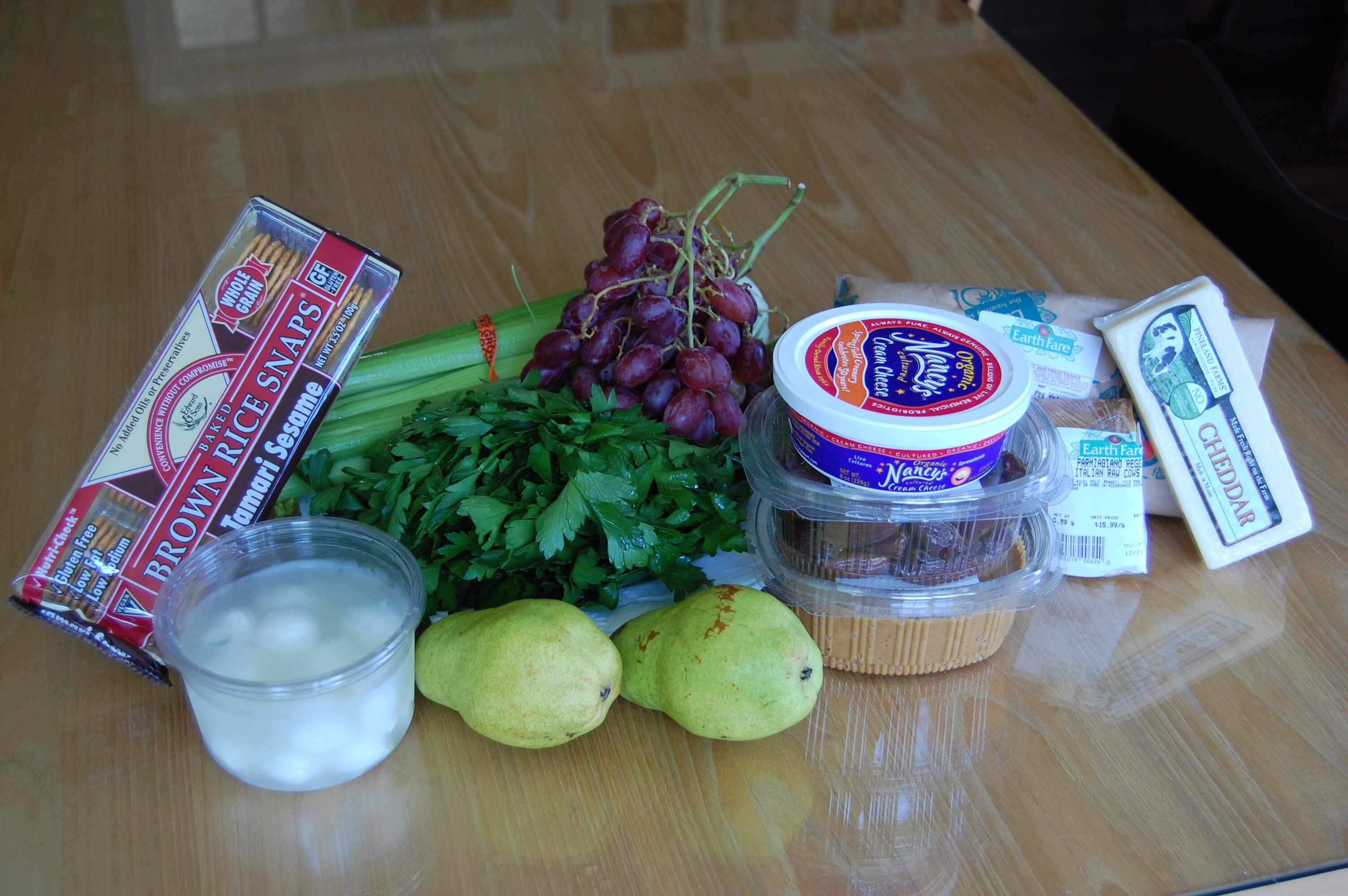 Groceries from Earthfare that include celery, dates, peanut butter, cheese, chicken breasts, frozen peas, brown rice crackers, grapes, pears, and parsley.