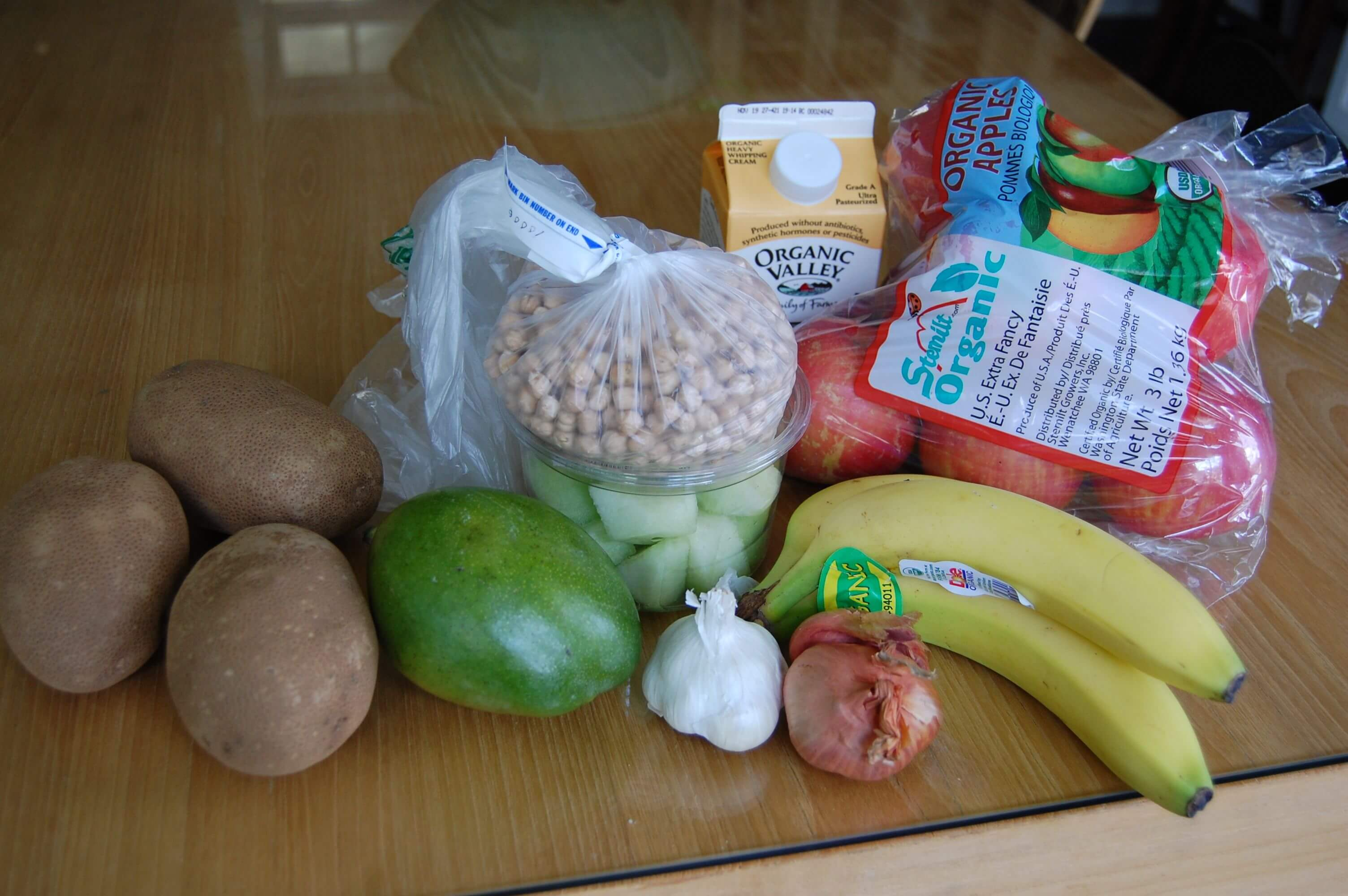 Groceries from Earth Fare that include fresh produce, beans, and heavy cream.