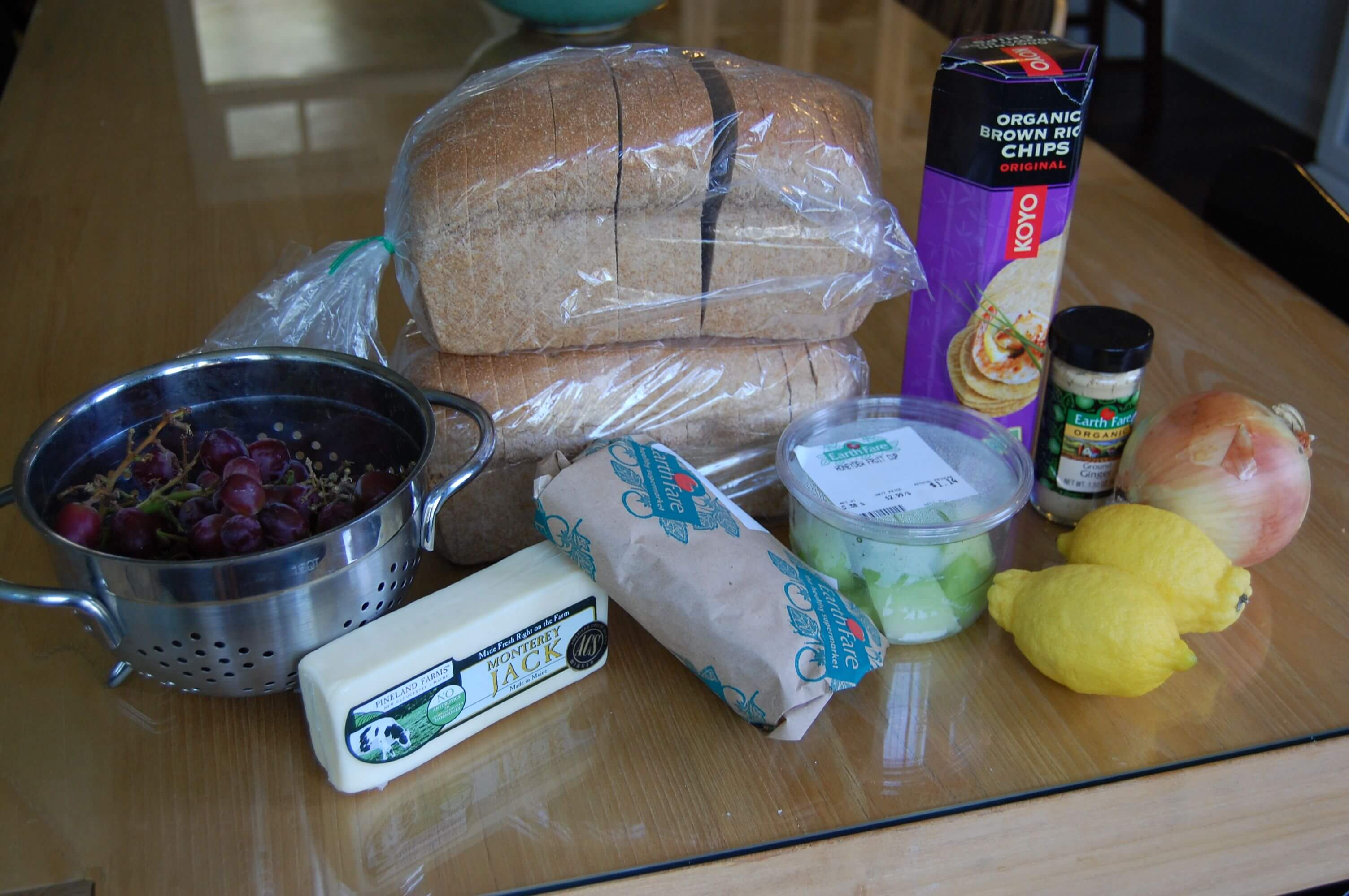 Groceries from Earthfare that include flounder, an onion, lemons, honeydew, grapes, cheese, whole-wheat bread, brown rice crackers, and ground ginger.
