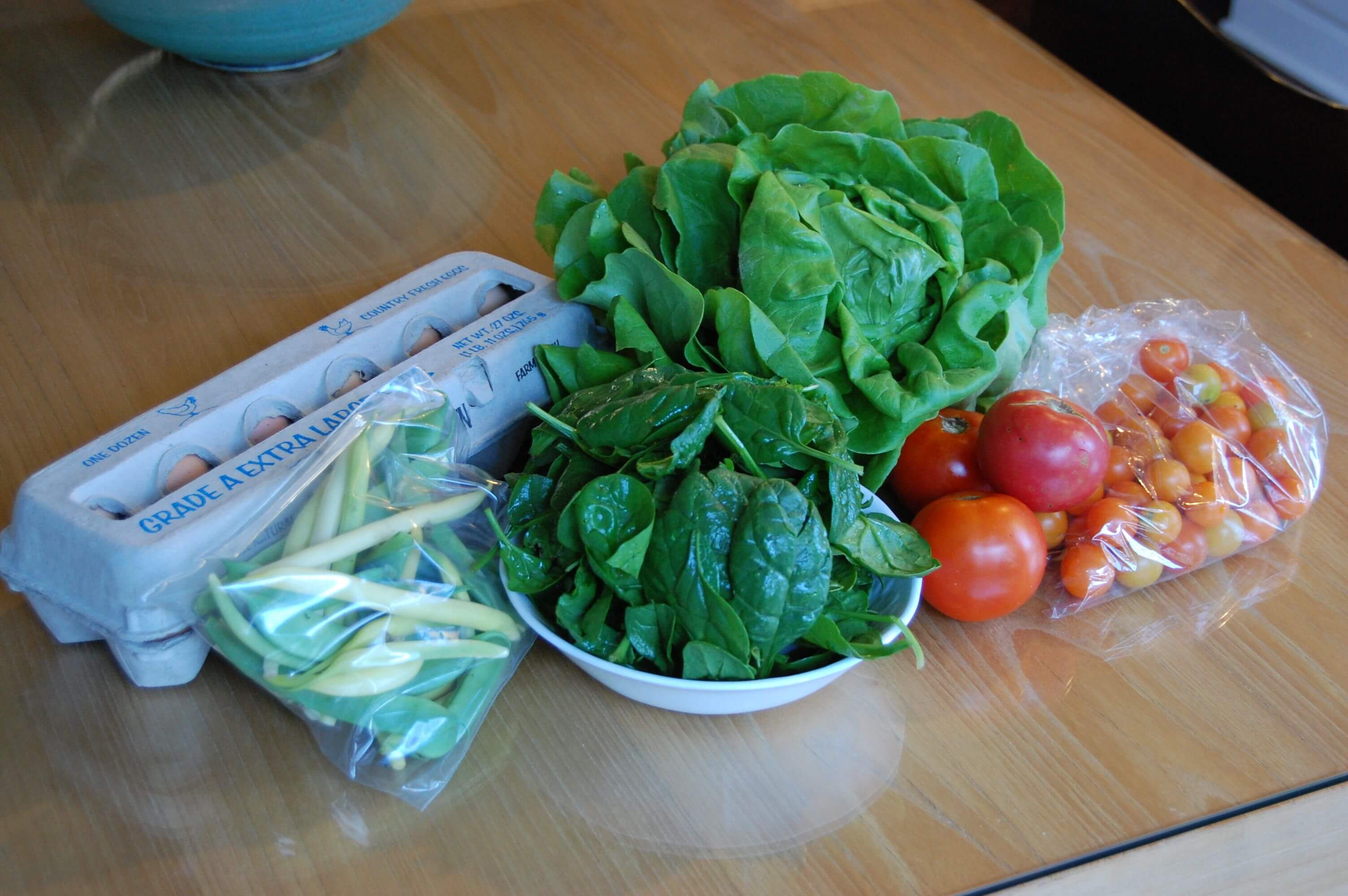 Fresh produce from the farmers market that includes eggs, lettuce, spinach, tomatoes, and green beans.