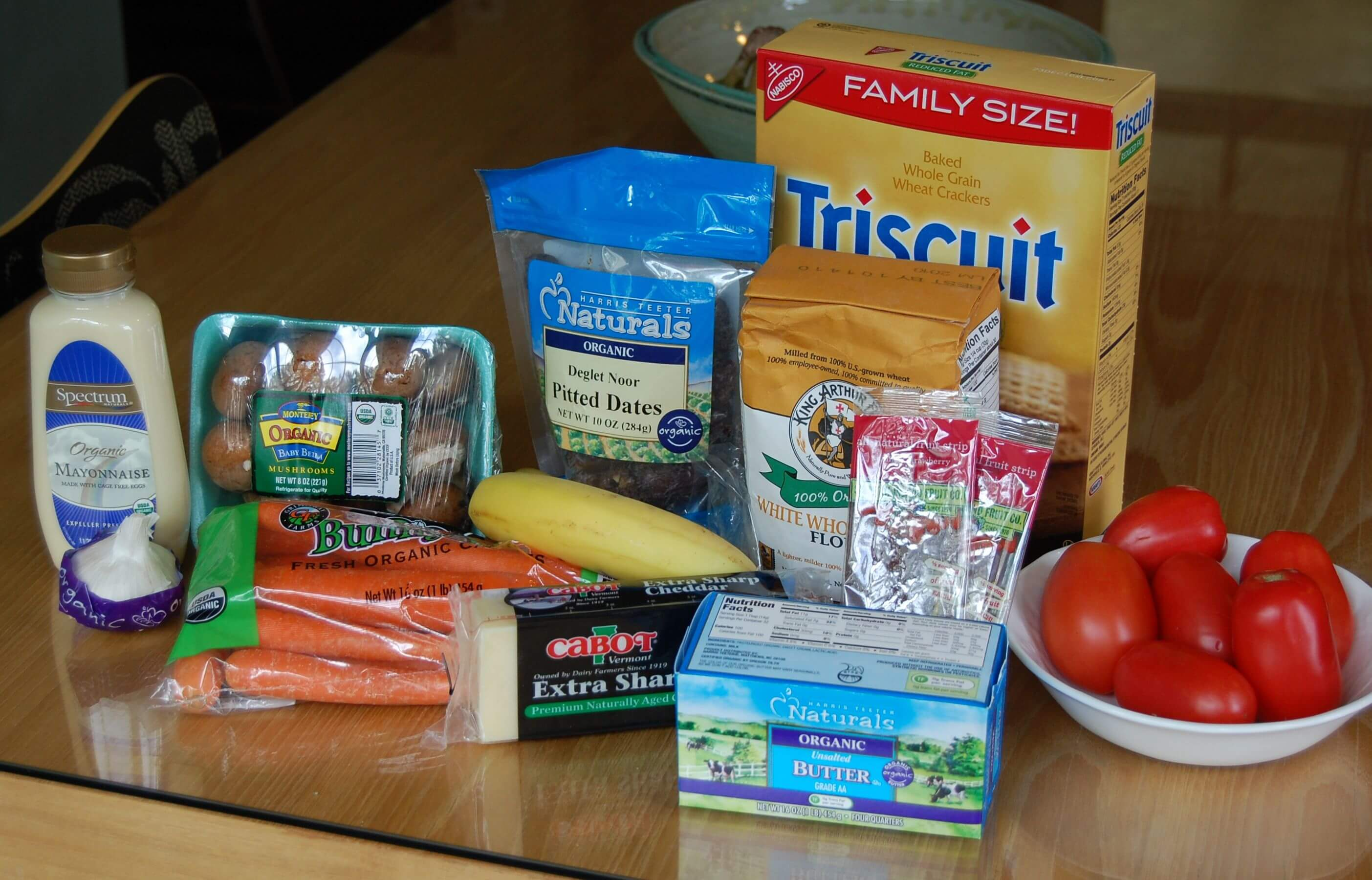 Groceries from Harris Teether that includes mayonnaise, Triscuits, dates, bananas, tomatoes, mushrooms, carrots, garlic, and cheese.