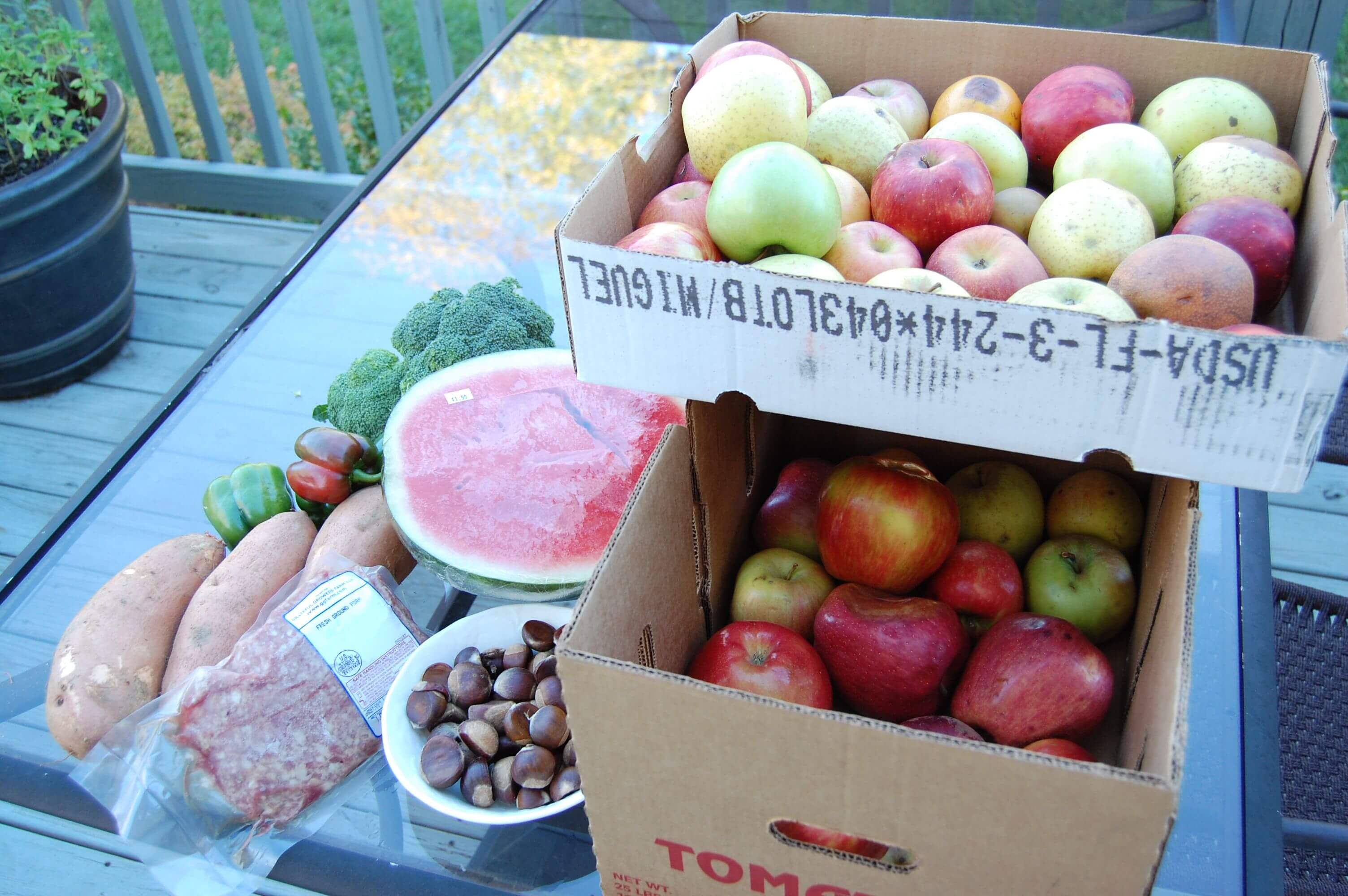 Boxes of apples, watermelon, sweet potatoes, broccoli, meat, and some nuts from the Hillbilly Produce in North Carolina.