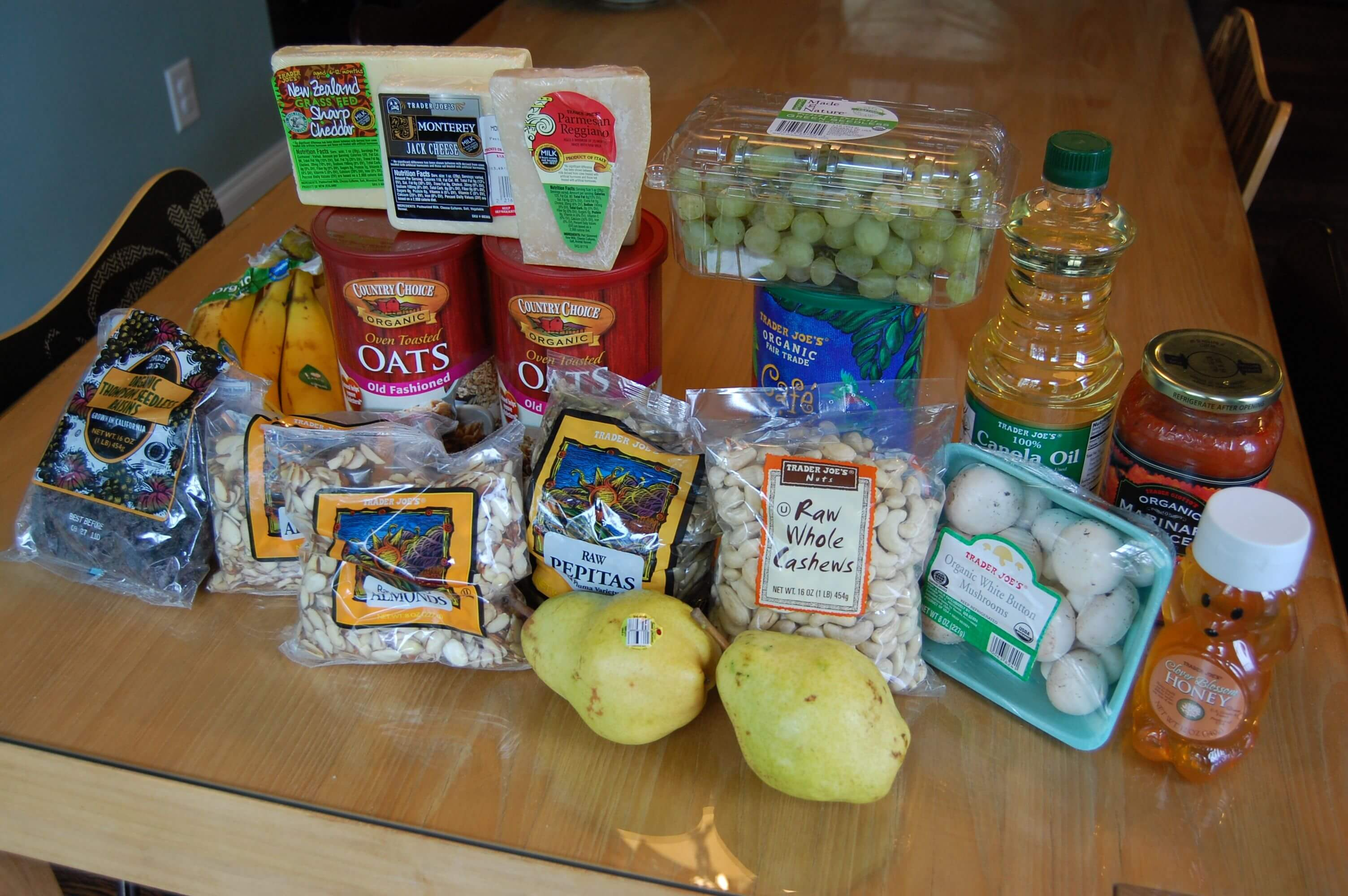 Groceries from Trader Joe's that include fruits, vegetables, nuts, and oats.