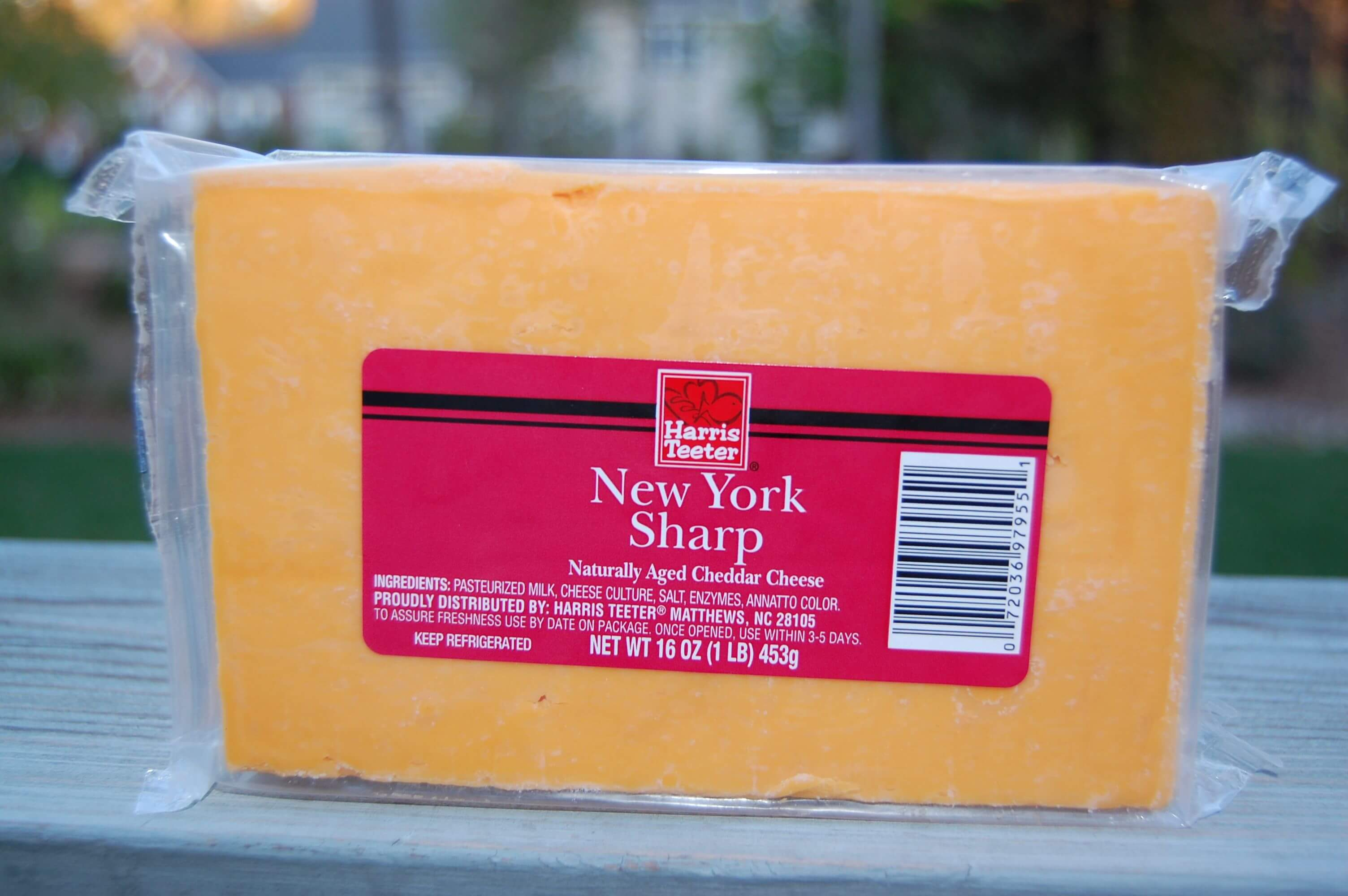 A block of packaged cheddar cheese from Harris Teeter.