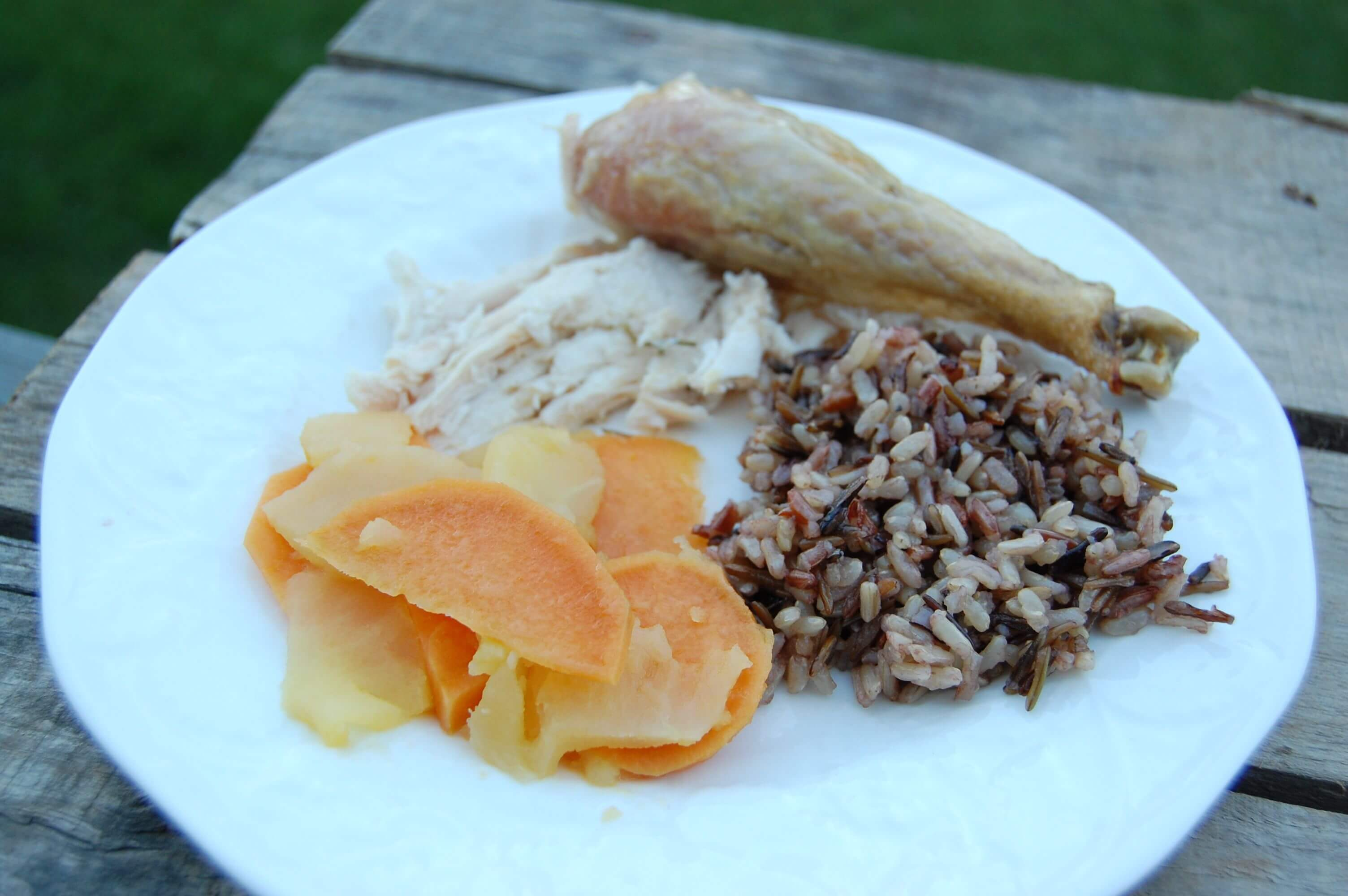 A plate of roasted chicken, wild rice, and sautéed sweet potatoes/apples.