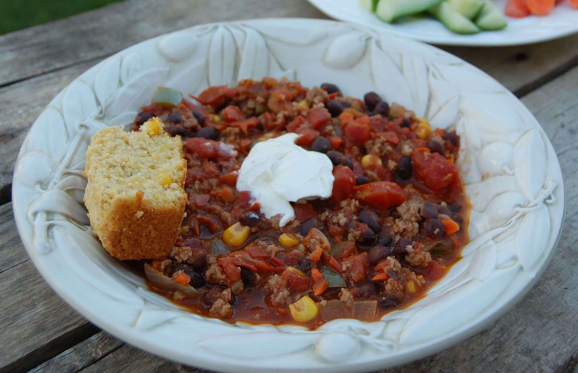 Homemade chili in a bowl with a side of cornbread.