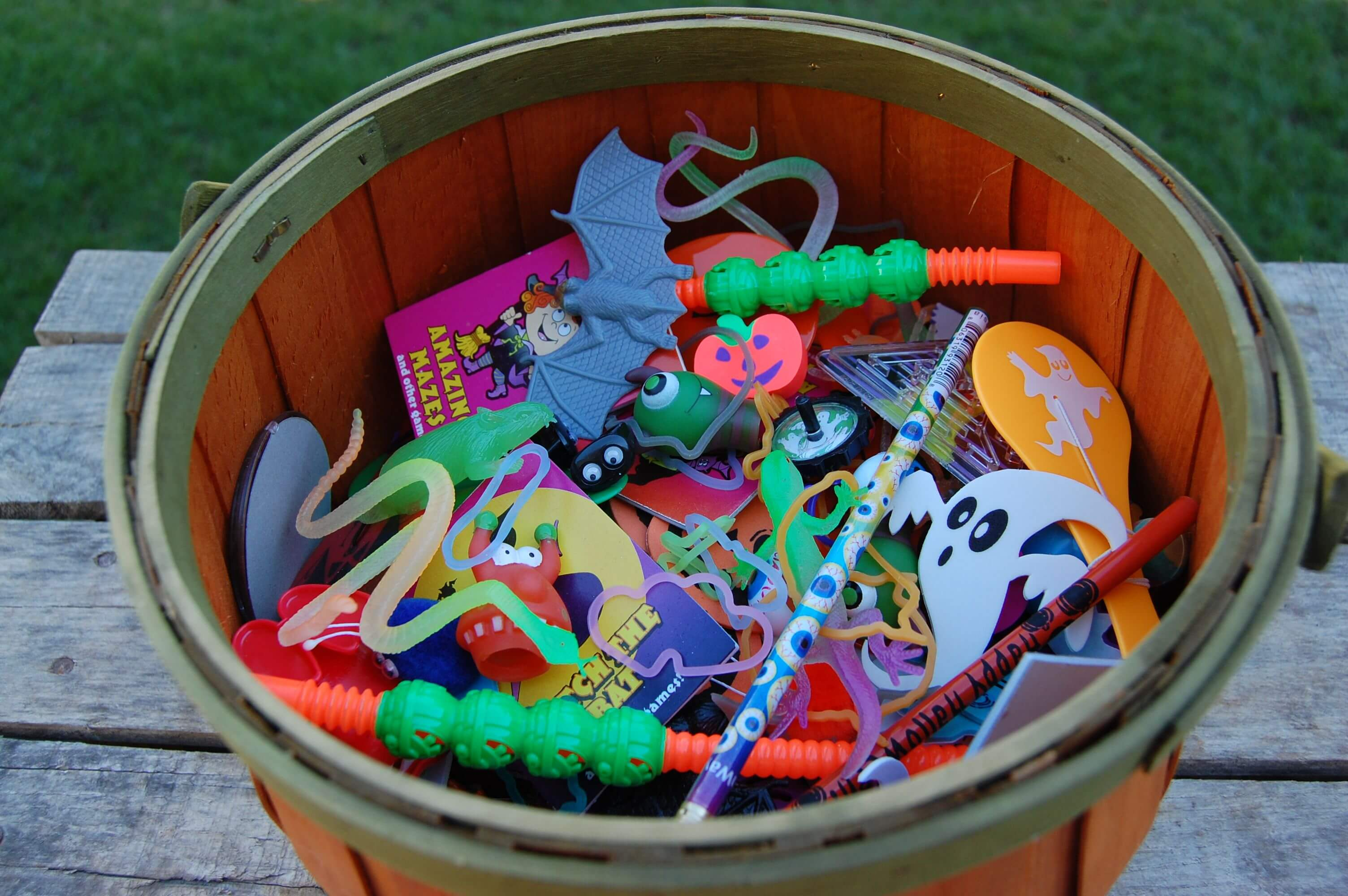A bin full of small kid toys for halloween.