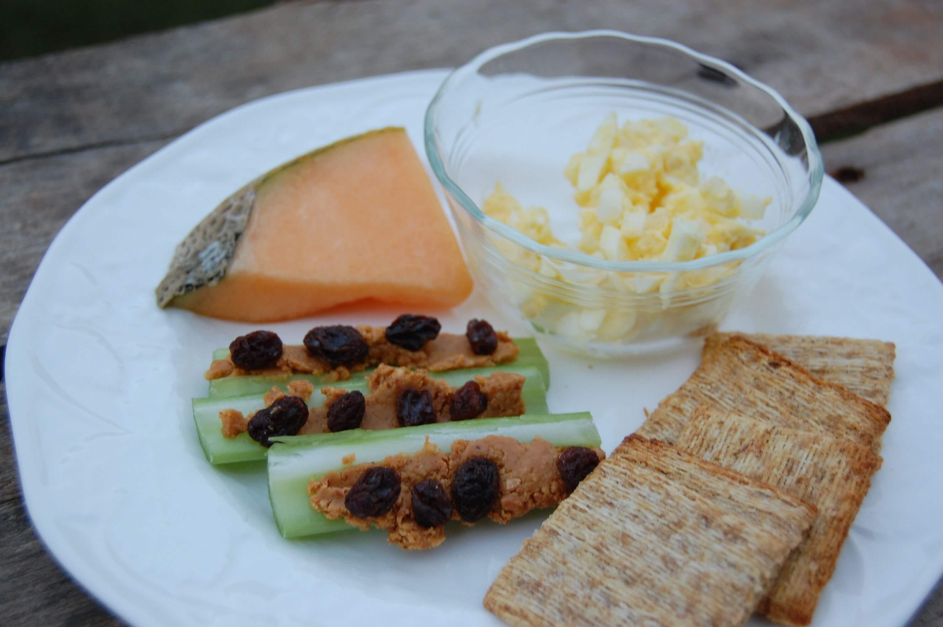 A plate of egg salad, crackers, celery with peanut butter & raisins, and a slice of cantaloupe.