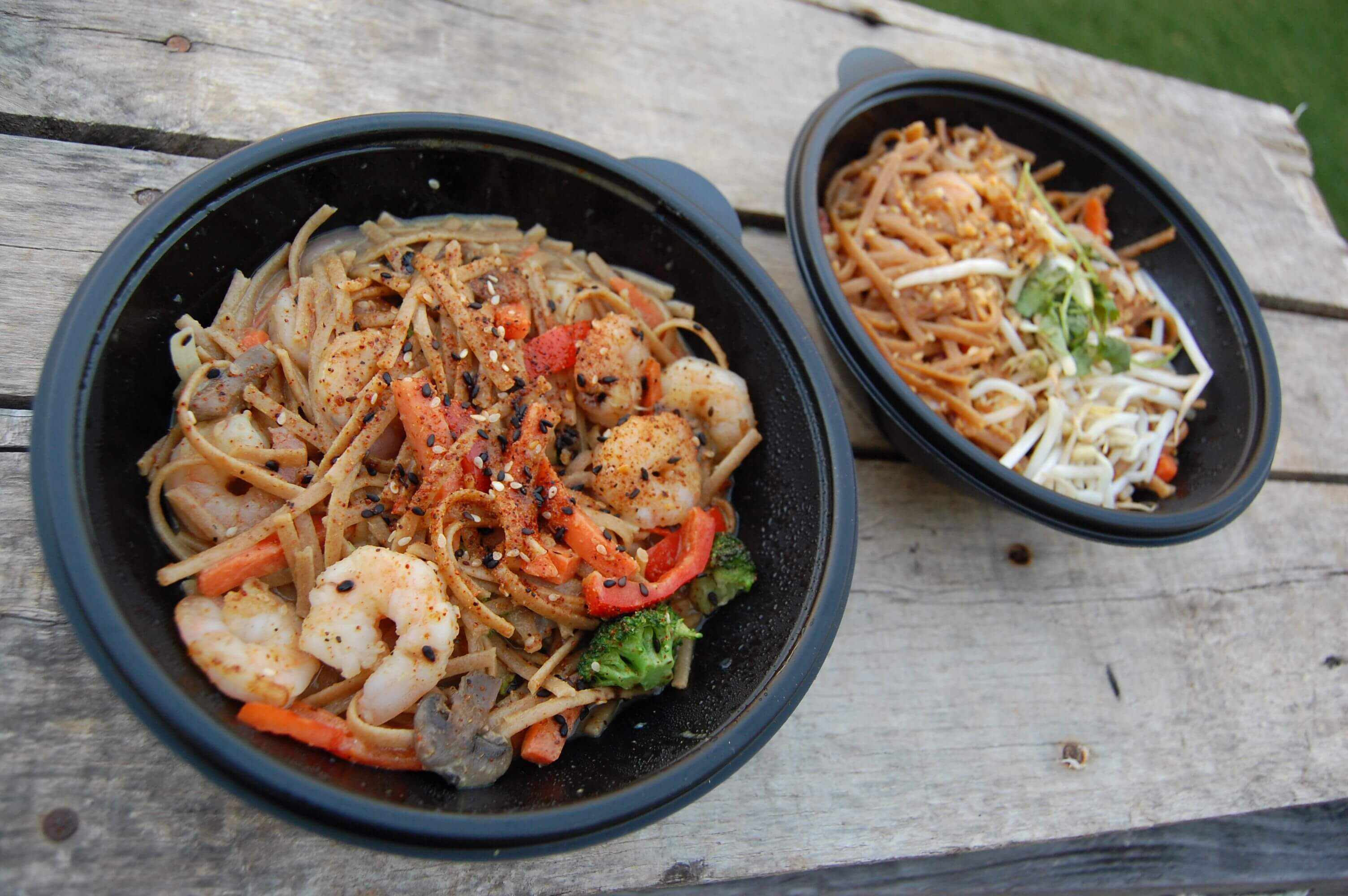 Two bowls of take-out Pad Thai and Curry.
